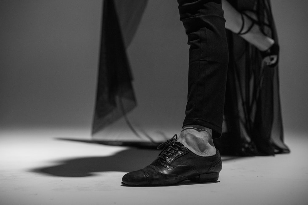 grayscale photo of person wearing black leather boots