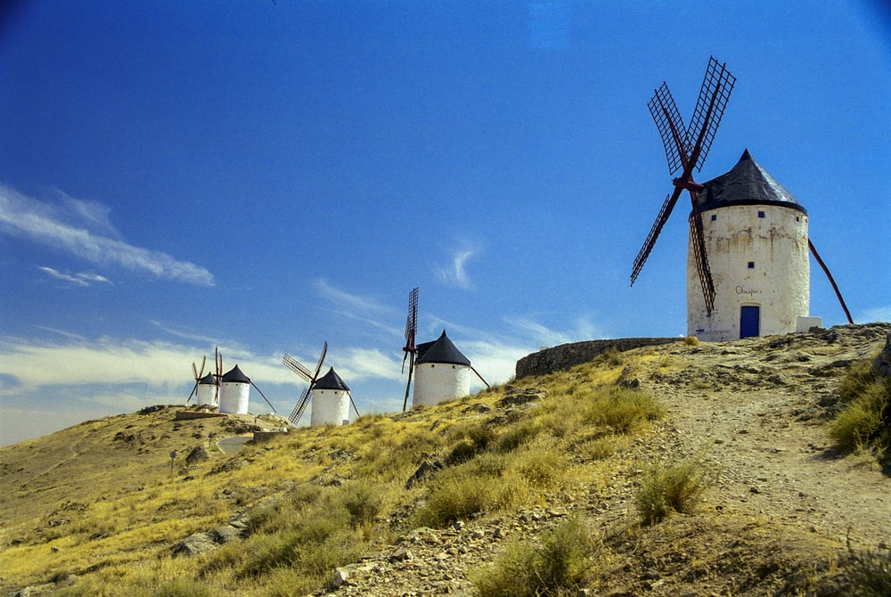 windmill on green grass field under blue sky during daytime