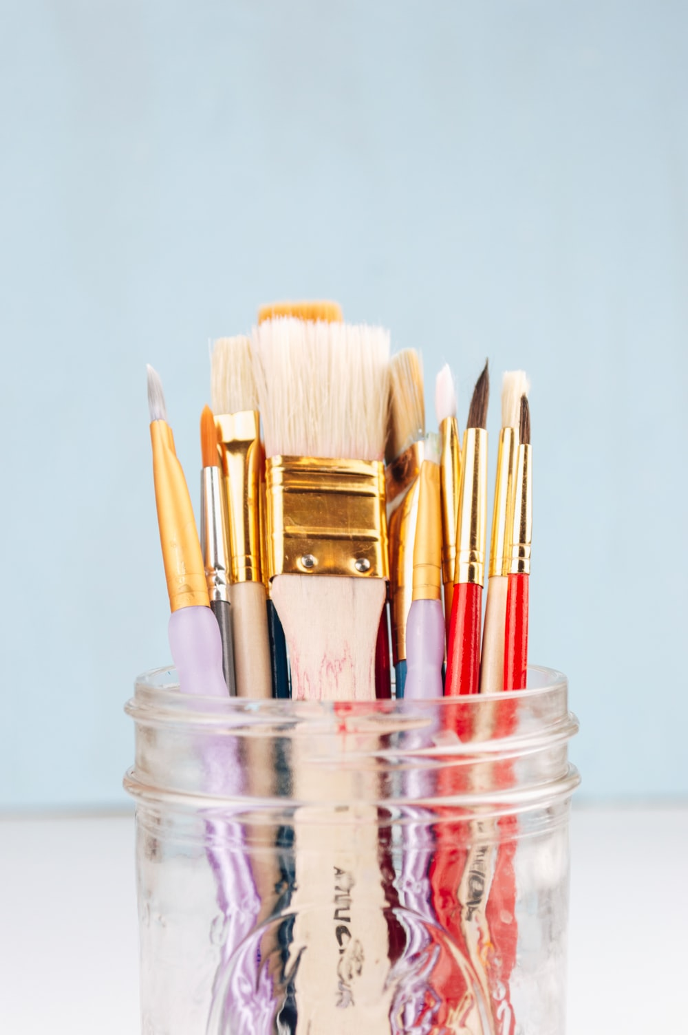 brown and red makeup brushes in clear glass jar