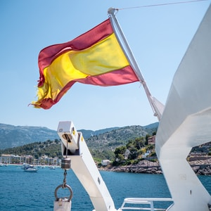 white and yellow flag on white boat during daytime