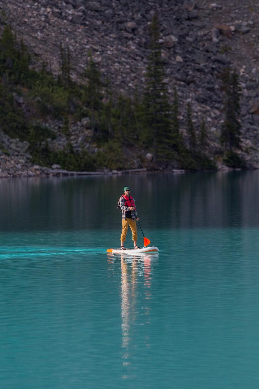 man in red shirt riding yellow kayak on blue water during daytime