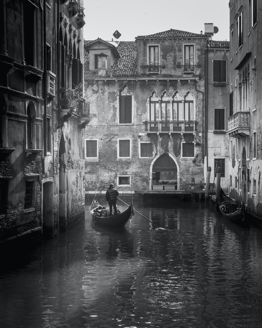 grayscale photo of boat on river between buildings