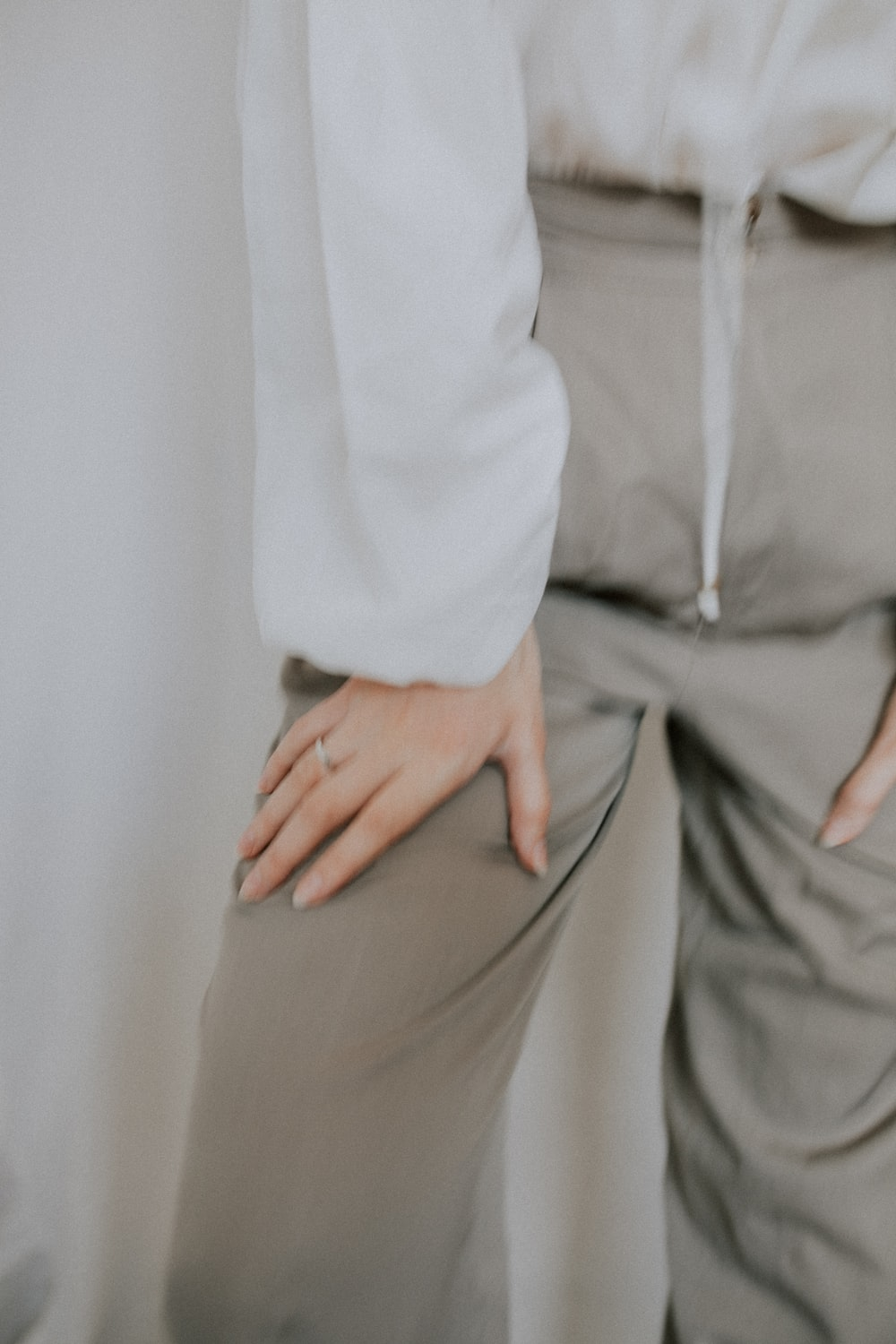 person in white dress shirt and gray pants