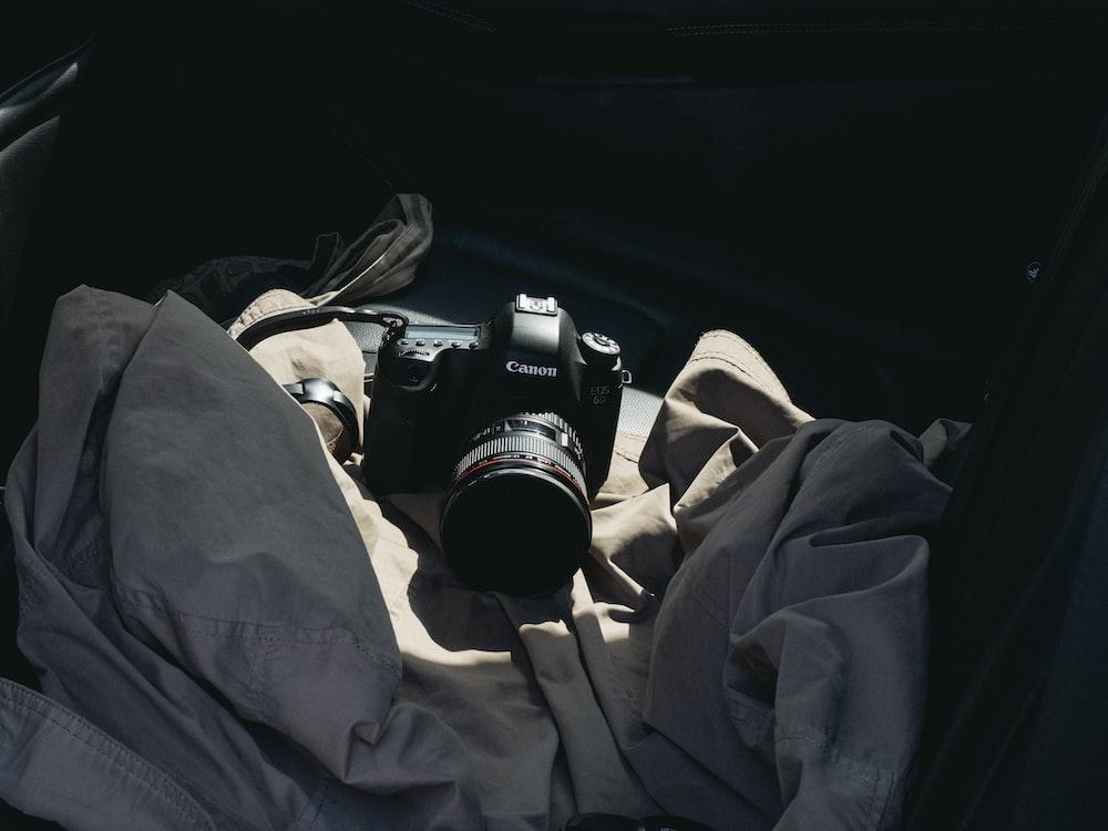 black dslr camera on brown textile