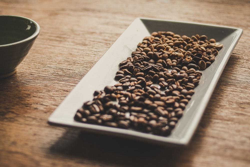 black and brown coffee beans on white ceramic tray