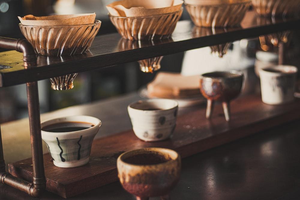 white ceramic bowls on brown wooden rack