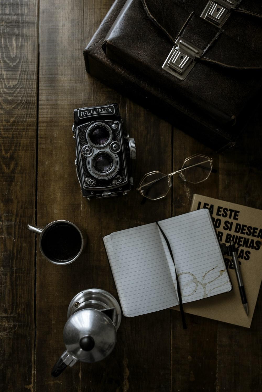 black nikon dslr camera beside white paper on brown wooden table