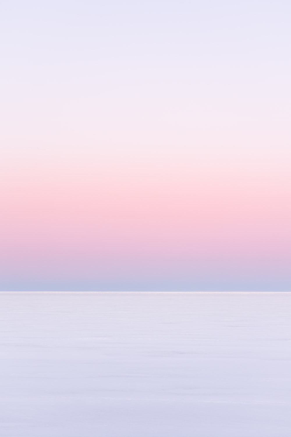 white and pink sky over the sea