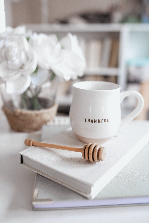 white ceramic mug beside brown wooden spoon