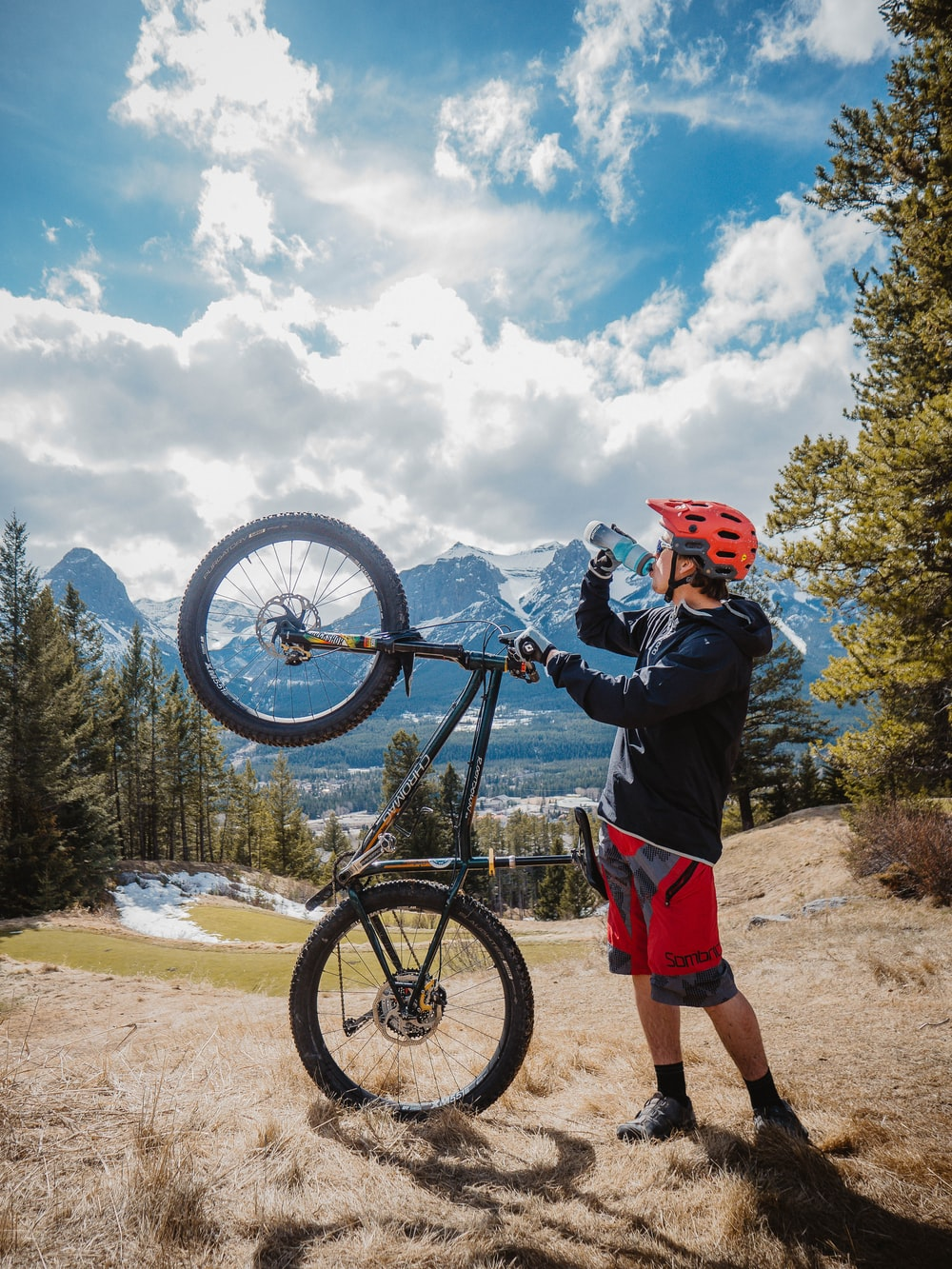 man in blue jacket and red shorts standing beside black mountain bike during daytime
