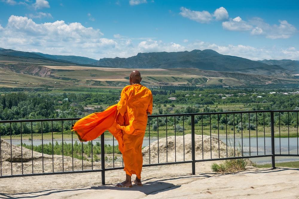 man in orange robe standing on gray concrete floor during daytime