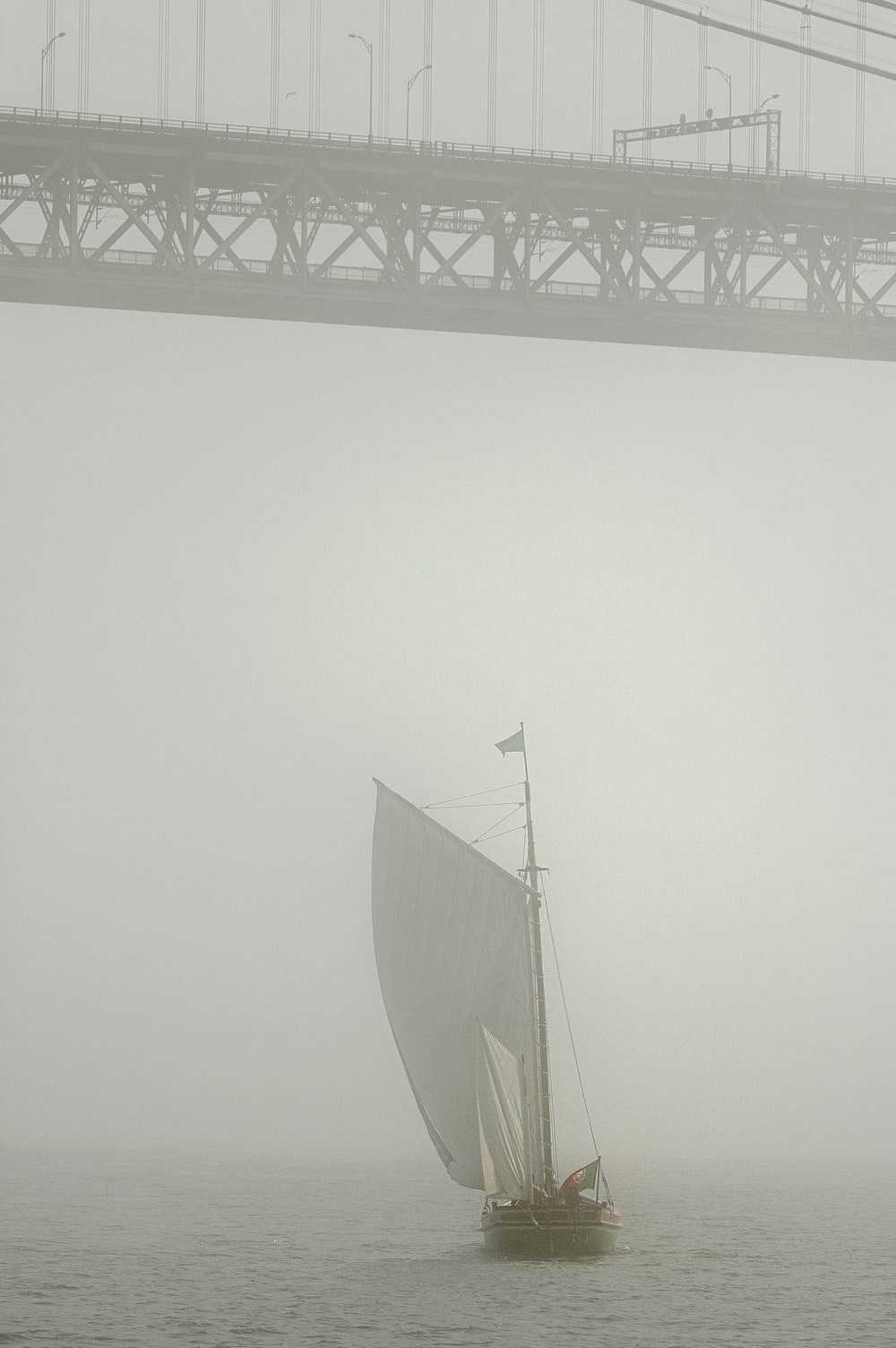 white sail boat on sea during foggy weather