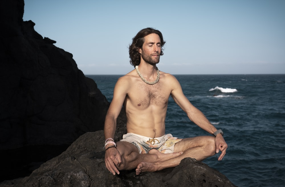 topless man in brown shorts sitting on rock near sea during daytime