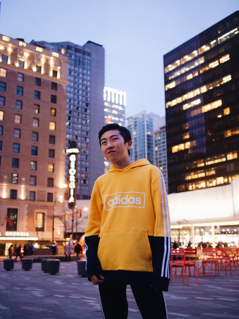 man in yellow hoodie standing on the street during daytime