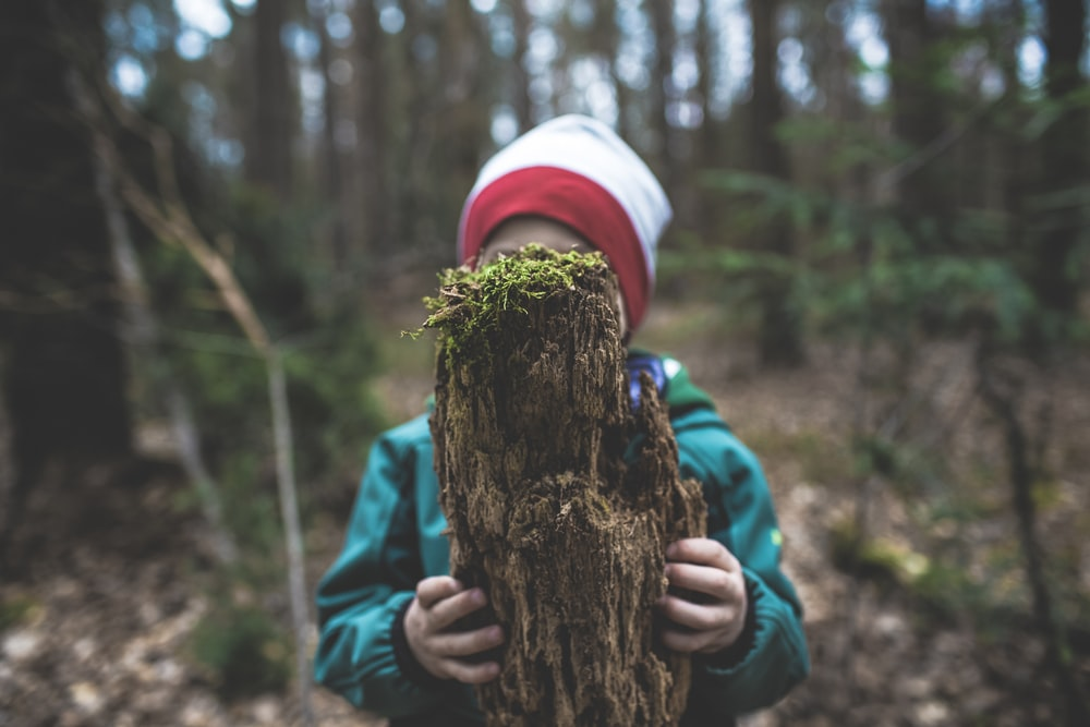 child in blue jacket and white knit cap holding brown tree trunk