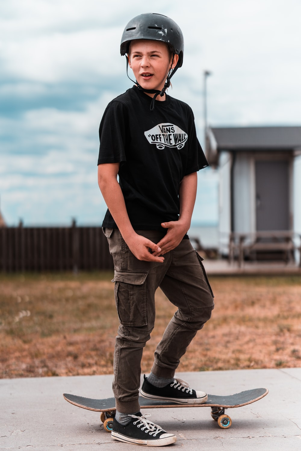 man in black crew neck t-shirt and brown denim jeans standing on brown grass field