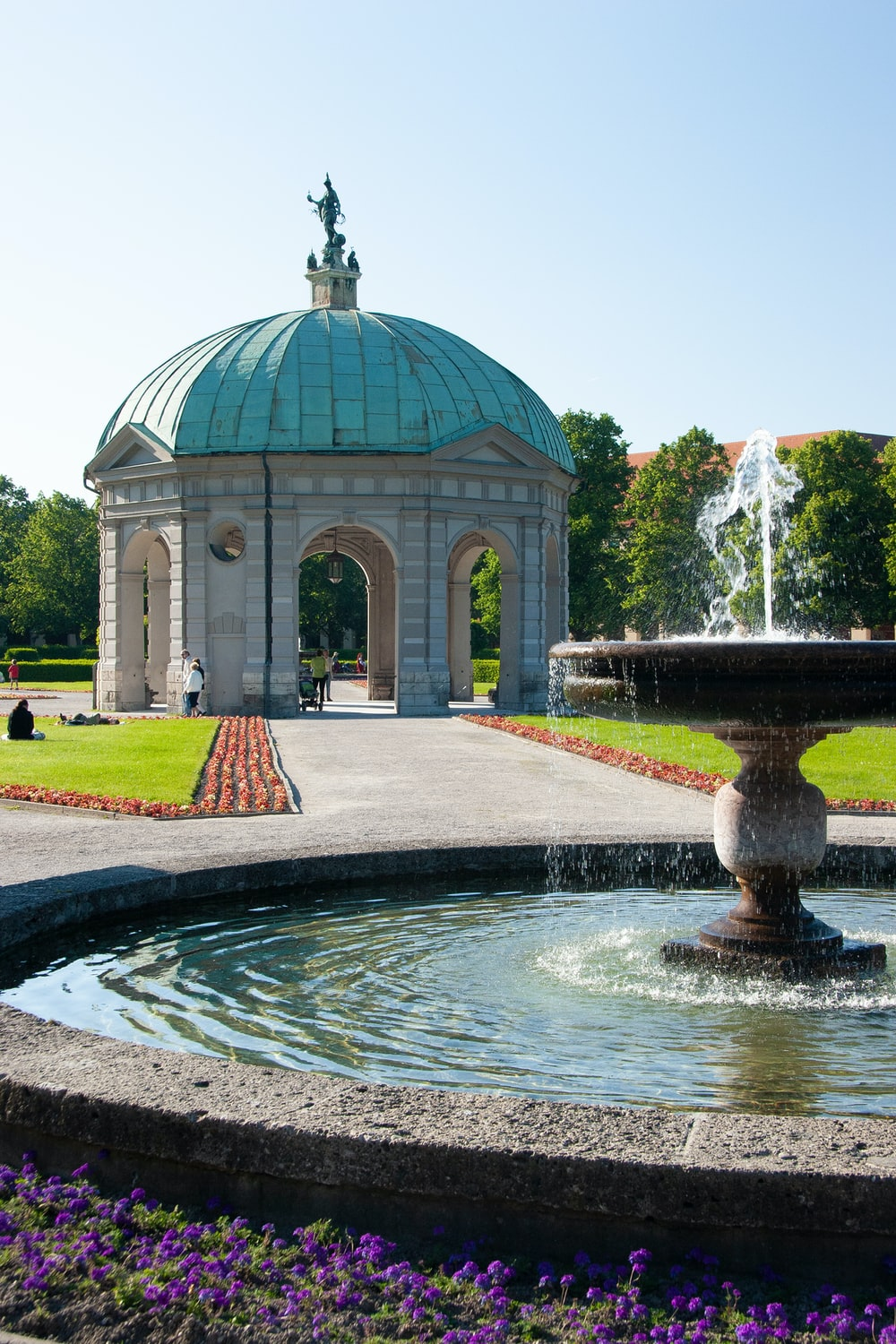 water fountain in front of white and green dome building