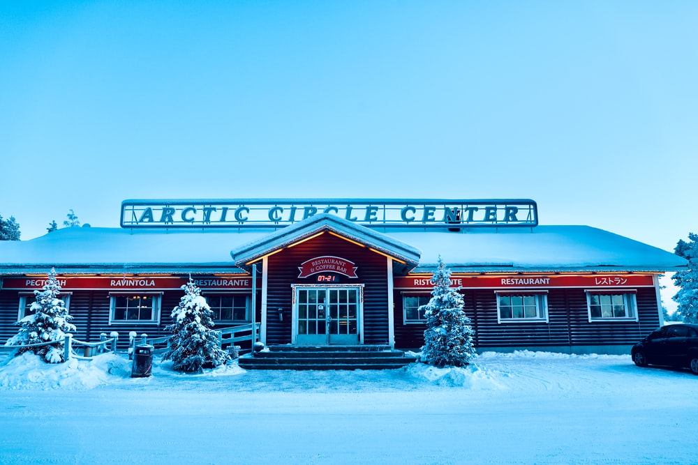 red and white wooden house with snow covered trees during daytime