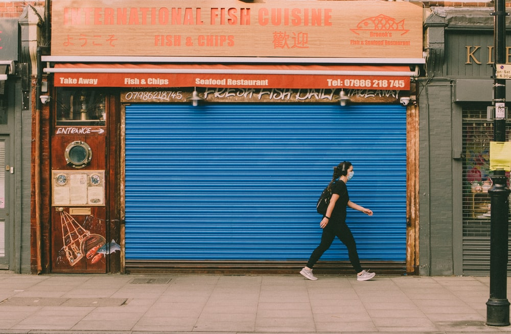 woman in black jacket and black pants standing beside blue roll up door during daytime