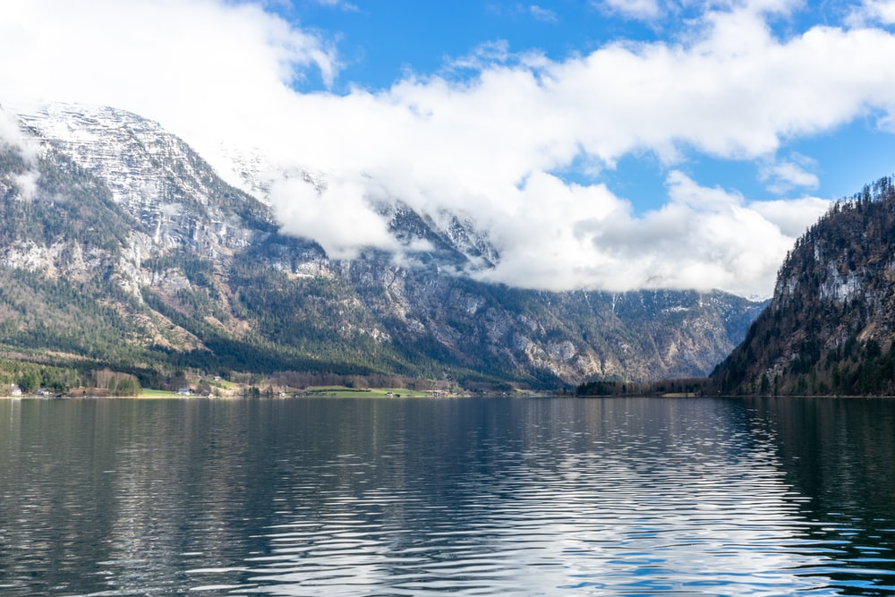 body of water near mountain under white clouds during daytime