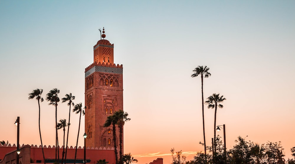 brown concrete building near palm trees during sunset