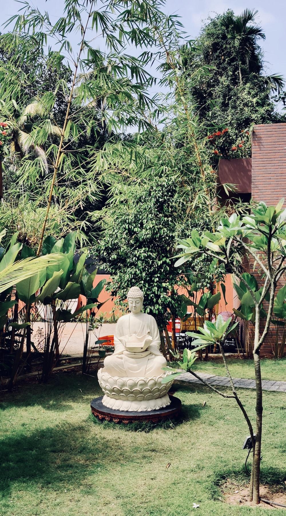 white ceramic statue near green tree during daytime