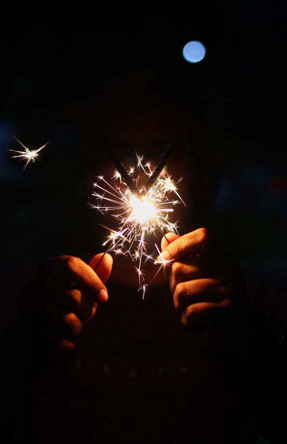 person holding lighted sparkler in dark room