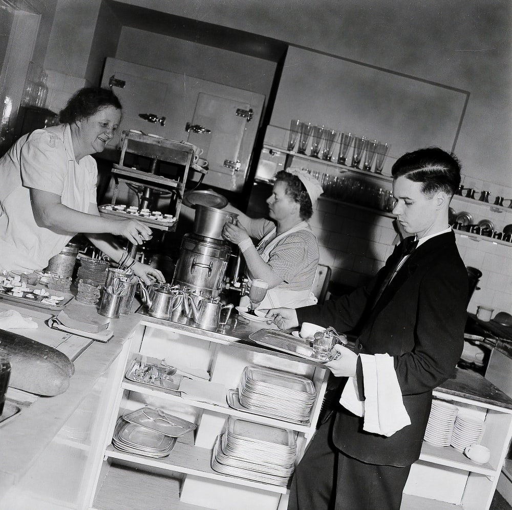 grayscale photo of man and woman standing in front of kitchen sink
