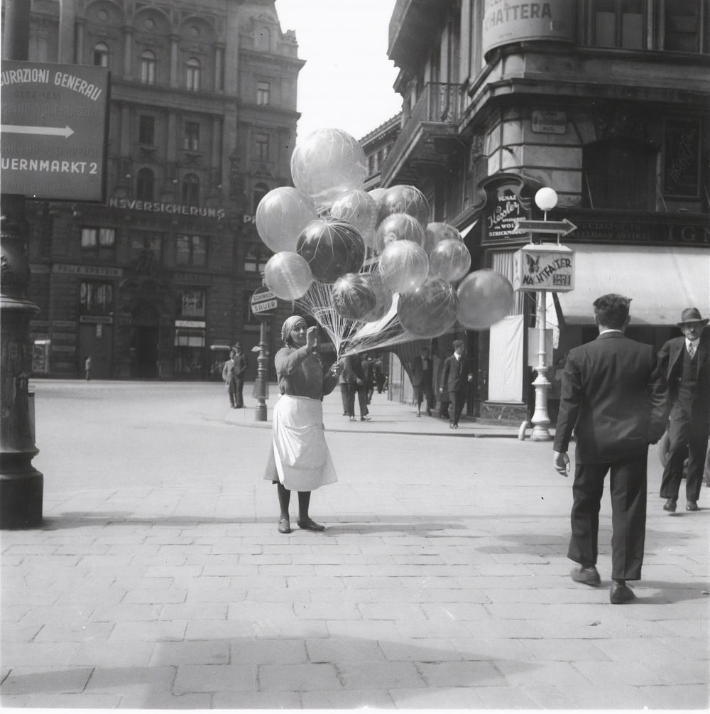 grayscale photo of people walking on sidewalk with balloons