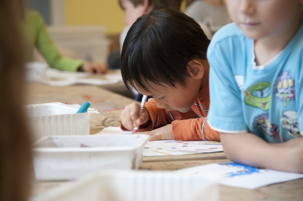 boy in blue t-shirt writing on white paper