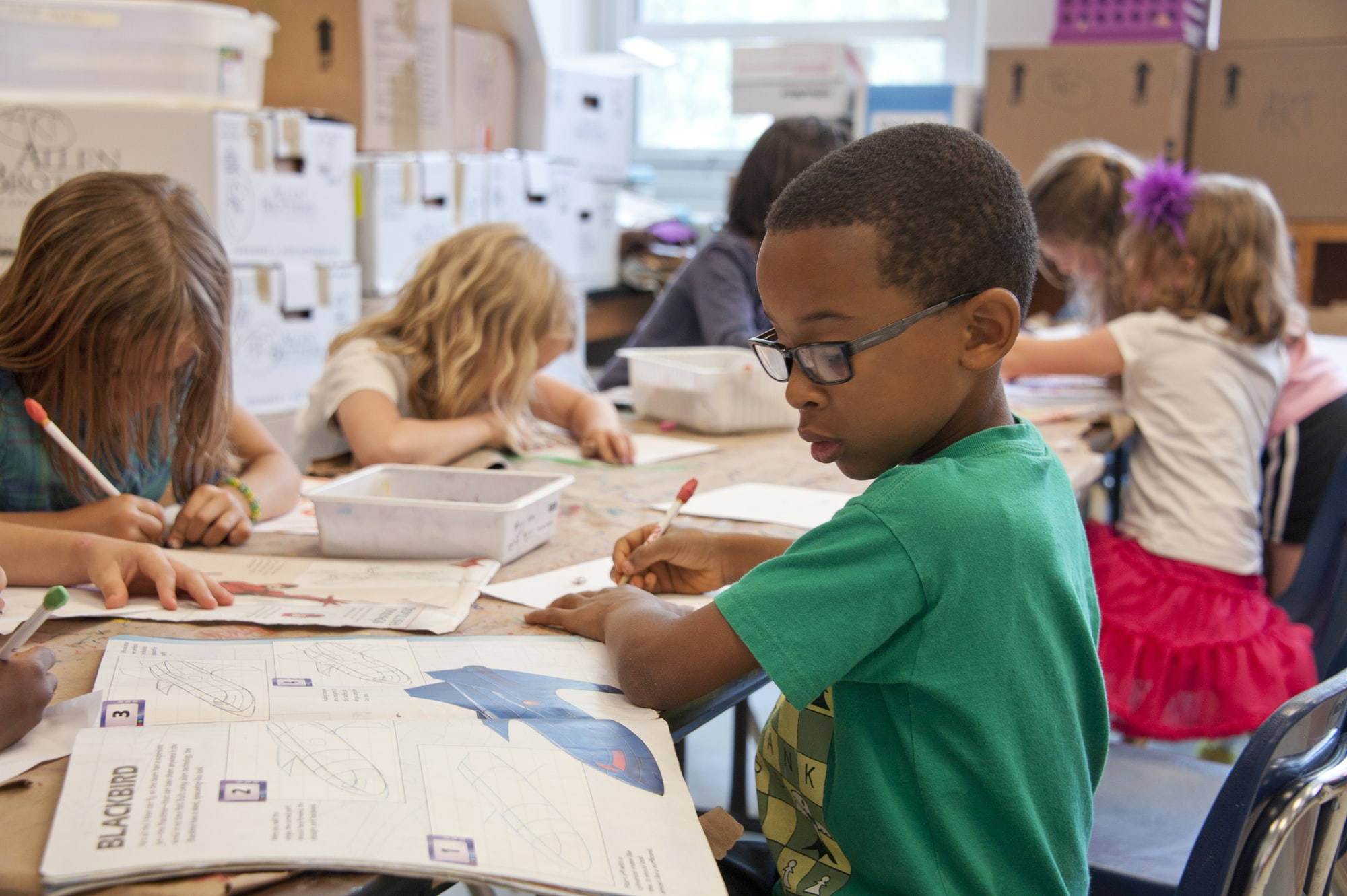 Captured in a metropolitan Atlanta, Georgia primary school, seated amongst his classmates, this photograph depicts a young African-American schoolboy who was in the process of drawing with a pencil on a piece of white paper. Note that the student was focused on a drawing book that referenced fantasy flying planes, while intent on creating his artwork, seemingly oblivious to all the classroom goings-on that surrounded him. It is important to know that objects, including pencils, crayons, paper, etc., are known as fomites, and can act as transmitters of illnesses.