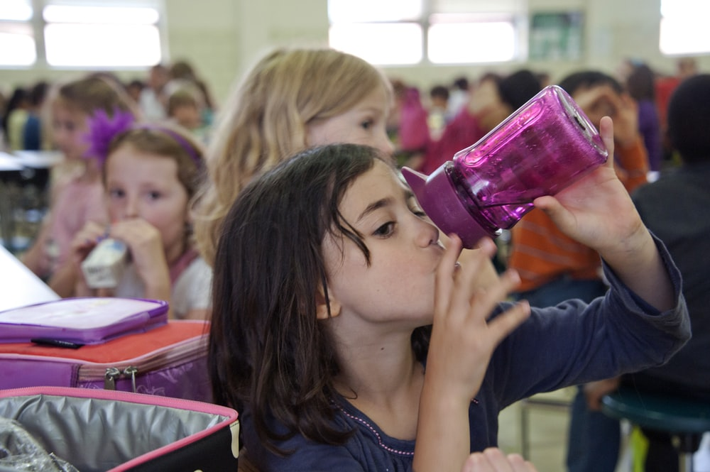 woman drinking from pink plastic cup