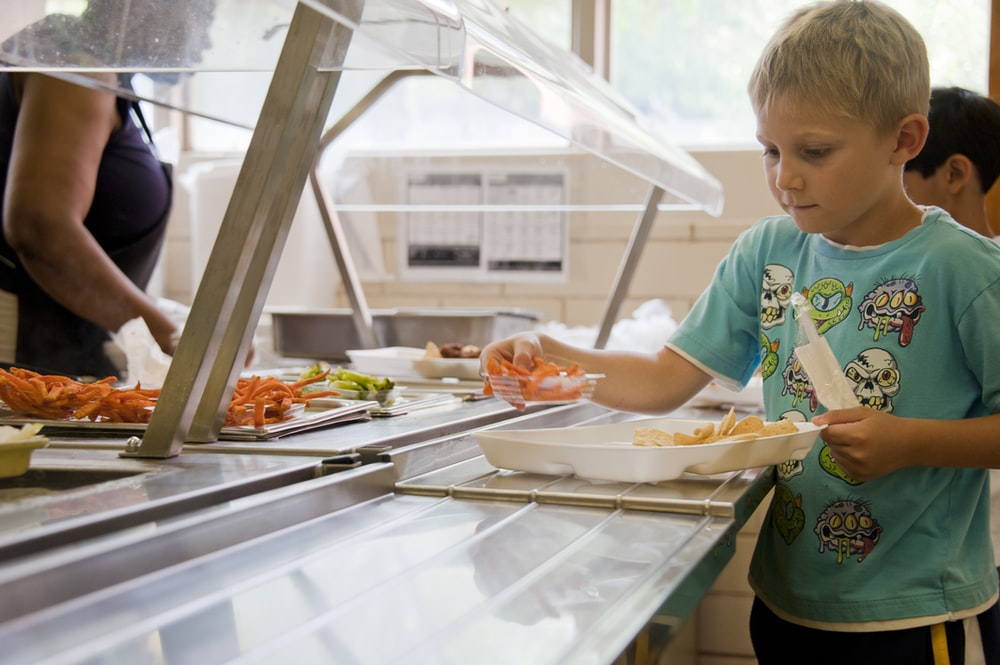 boy in green crew neck t-shirt standing in front of food on table