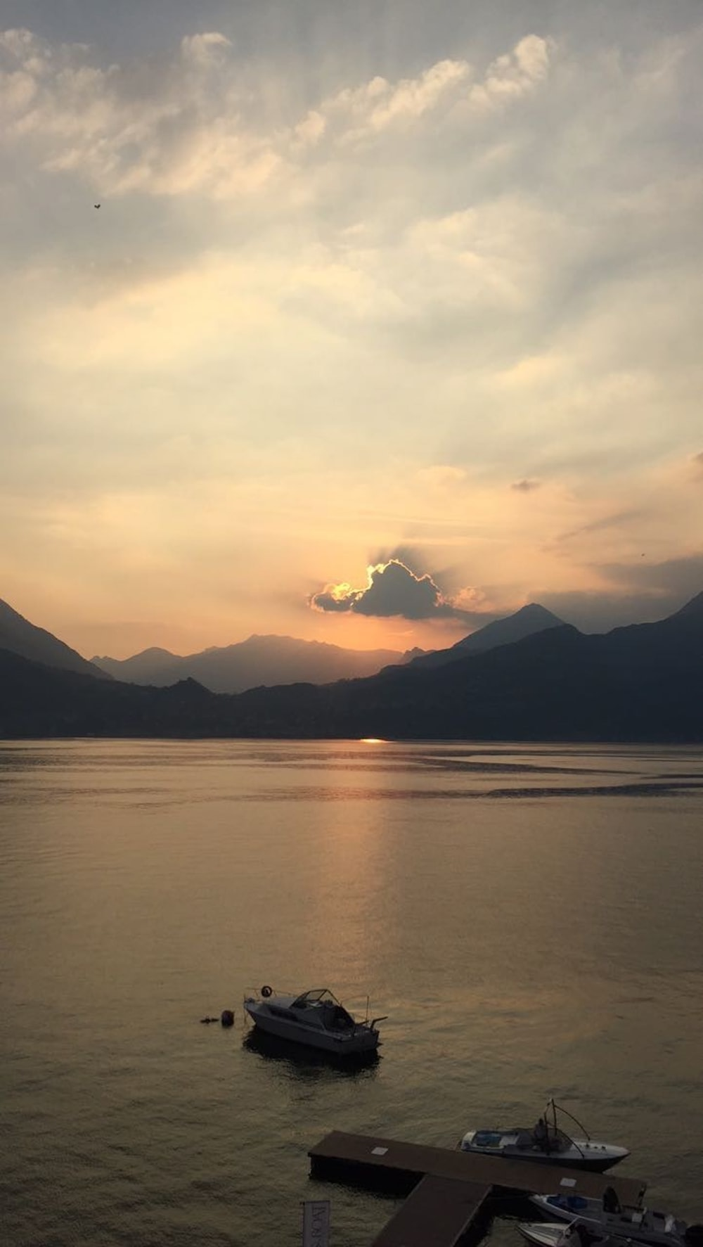 silhouette of mountains near body of water during sunset