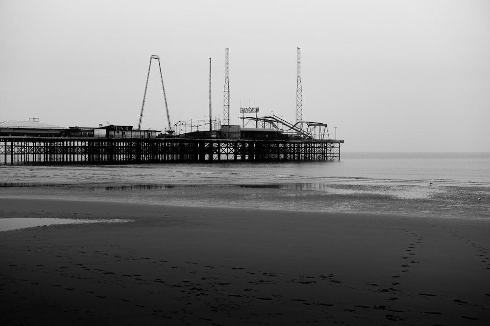 grayscale photo of dock on sea