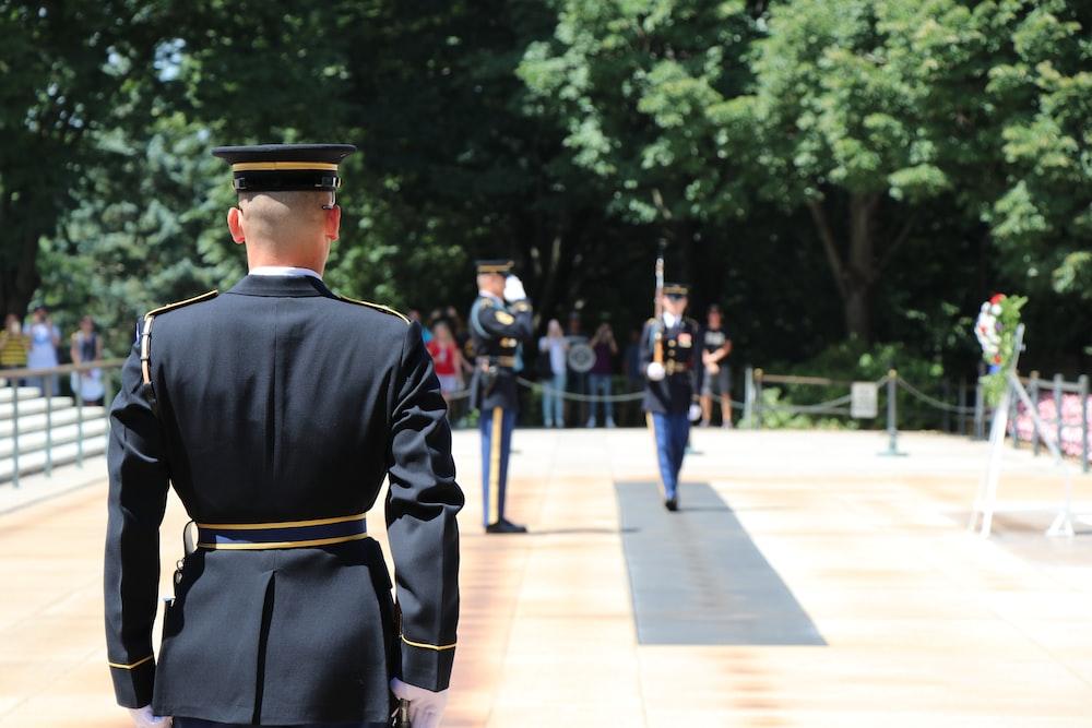 man in black uniform standing on gray concrete floor during daytime