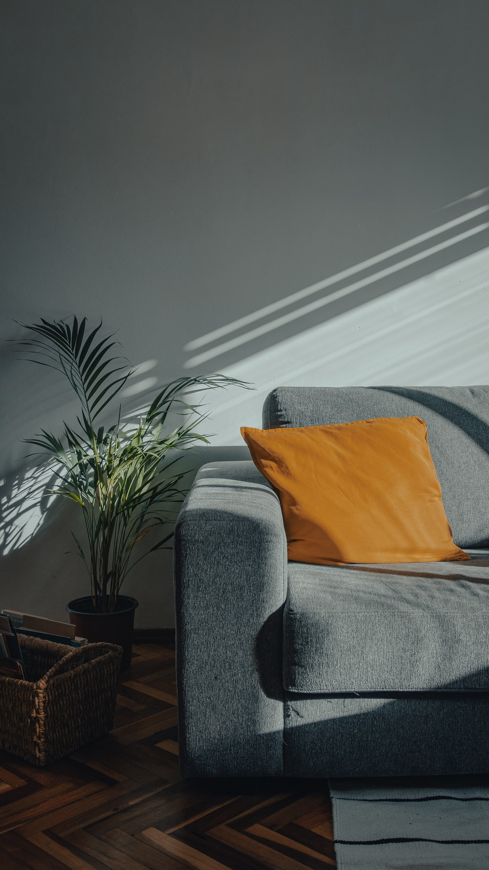 orange throw pillow on gray couch