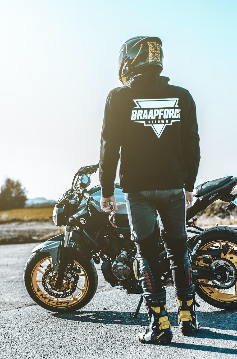 man in black hoodie and blue denim jeans standing beside black motorcycle during daytime