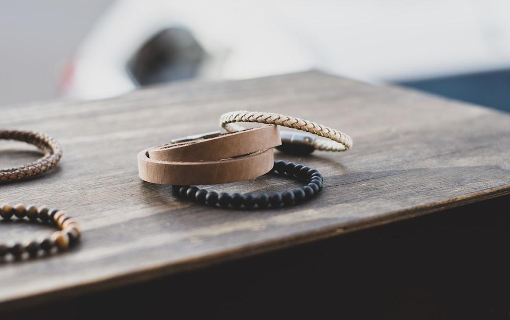 gold bracelet on brown wooden table