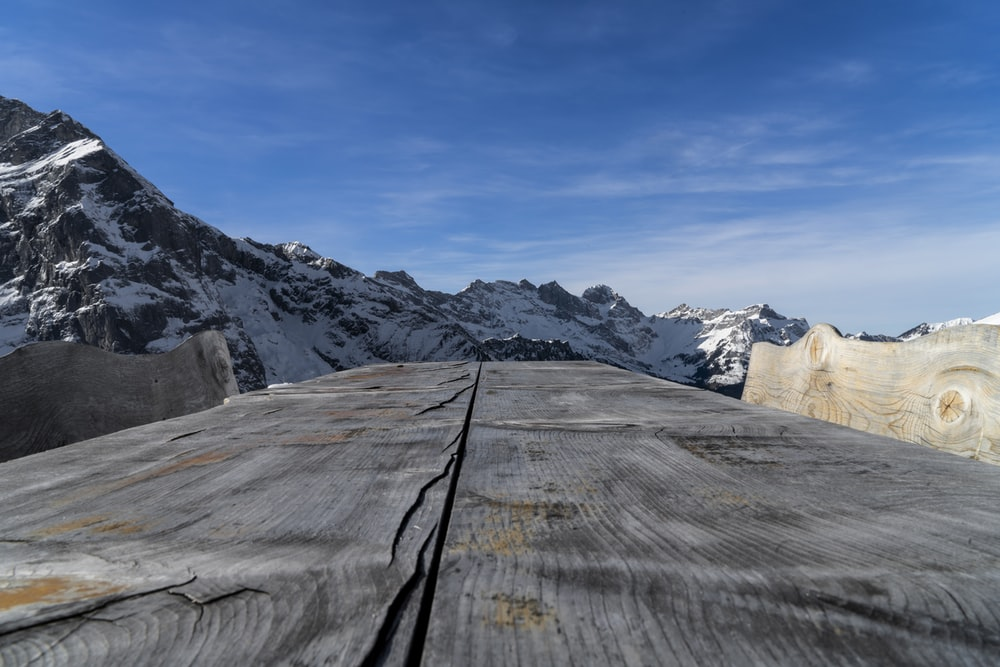 brown wooden fence on brown rocky mountain under white clouds and blue sky during daytime
