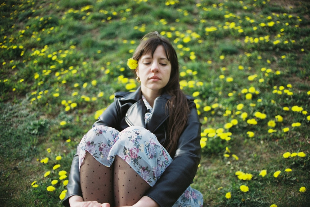 woman in black jacket sitting on yellow flower field during daytime