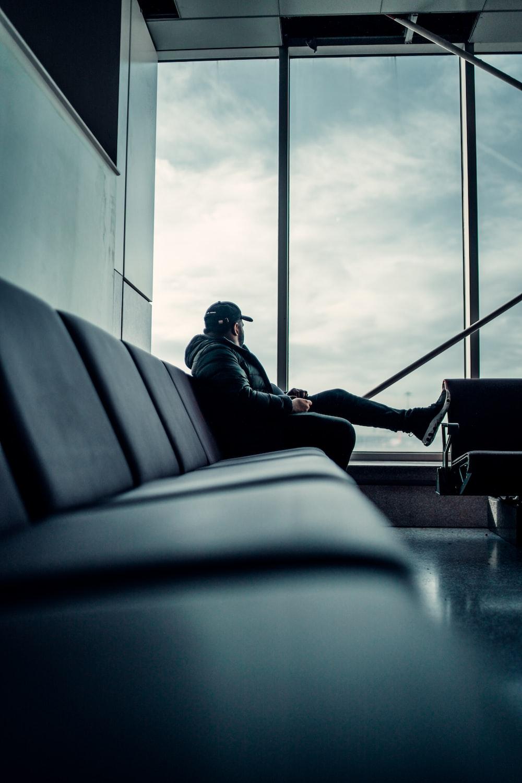 man in black jacket sitting on train seat