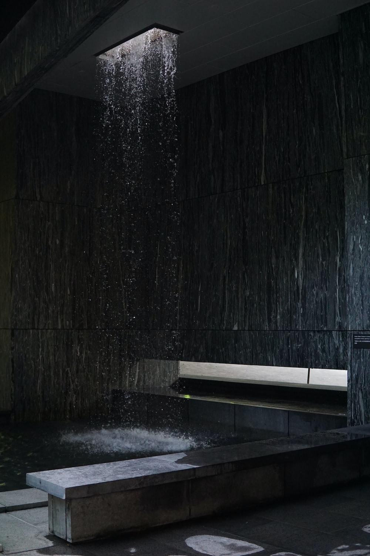 black wooden bench beside black concrete wall