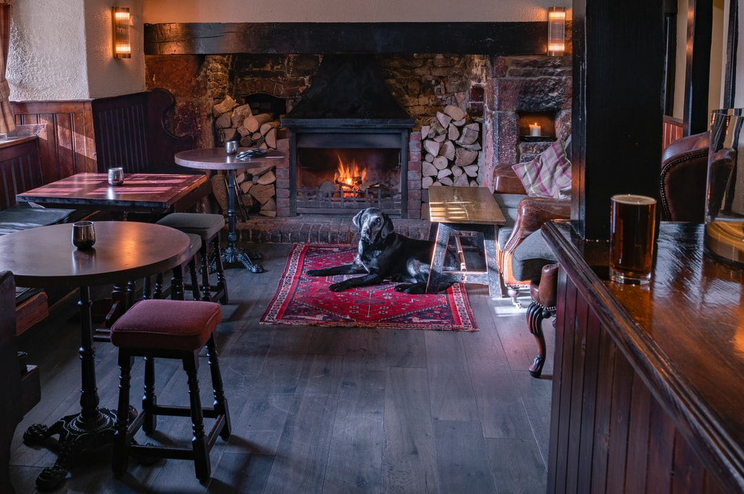 A black labrador sits quietly by the fire in an English pub in Somerset. Part of a commercial shoot for a pub group. Michael Cummins Photography - www.michaelcummins.co.uk