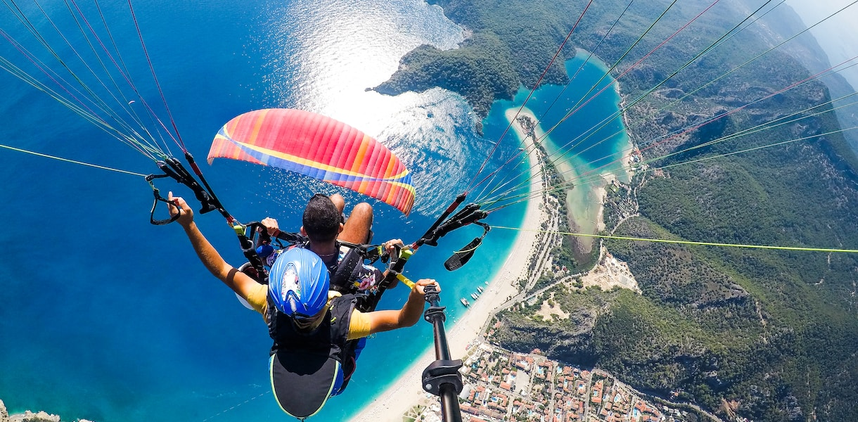 man in blue and black jacket riding on blue and white parachute