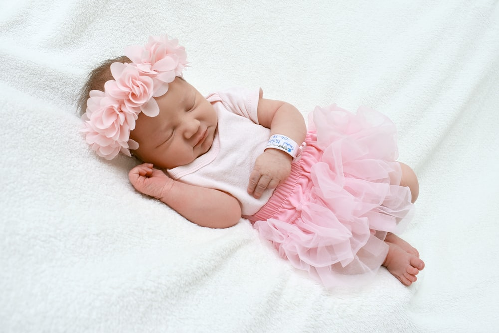 baby in pink dress lying on white textile