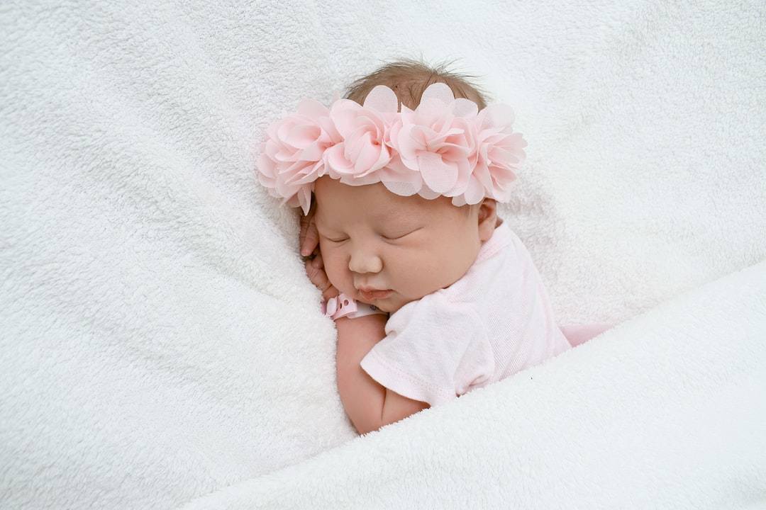 baby in white shirt lying on white textile