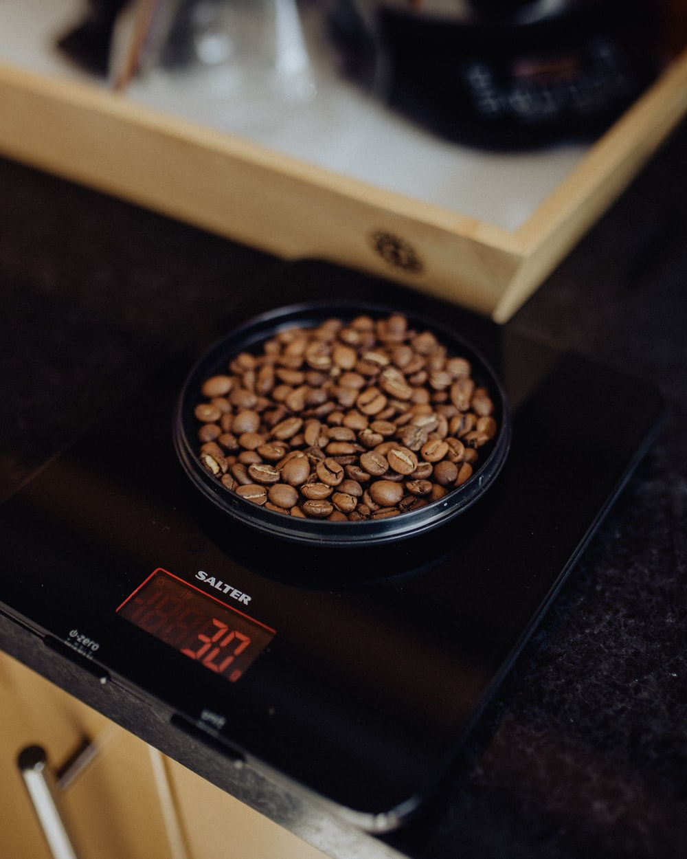 brown round container on black digital weighing scale