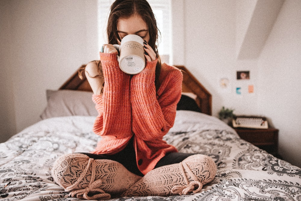 woman in red knit sweater holding white ceramic mug