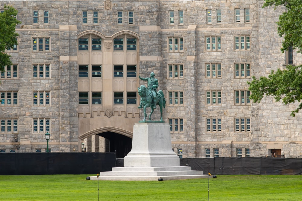 man riding horse statue near brown building during daytime